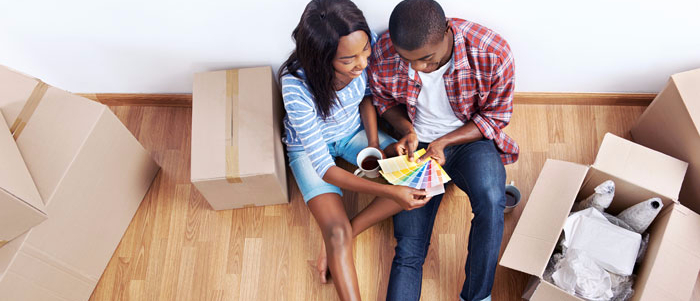 Mixed-race couple sitting in the floor of their home comparing paint chips.  They are surrounded by boxes suggesting they've just moved in.