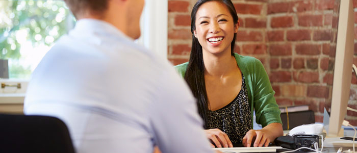 Male employment applicant talking to female HR director.  They are smiling.