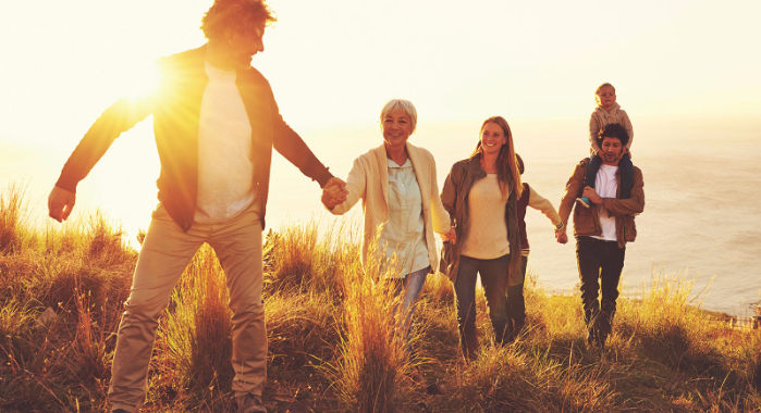 Multi-generational family walking and holding hands on a hill overlooking a lake or the ocean at sunset.