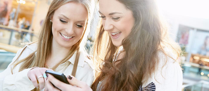 College aged girls out shopping and smiling while looking at cell phone.