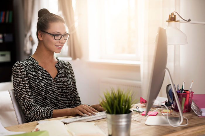 Female business owner working online in her home office.