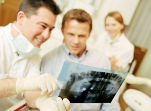 Male dentist explains x-ray to male patient while female hygienist looks on.