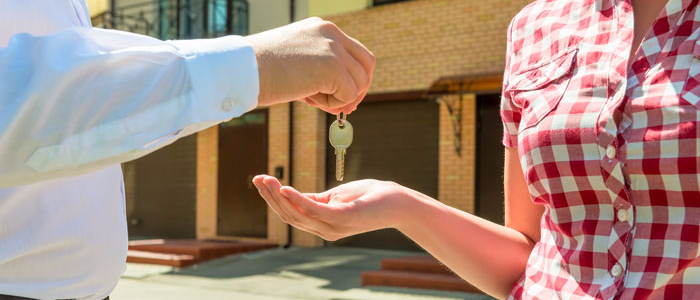 Property manager handing keys to his new tenant in front of her new apartment building.